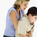 side view of a woman performing the Heimlich maneuver on a boy (10-12)